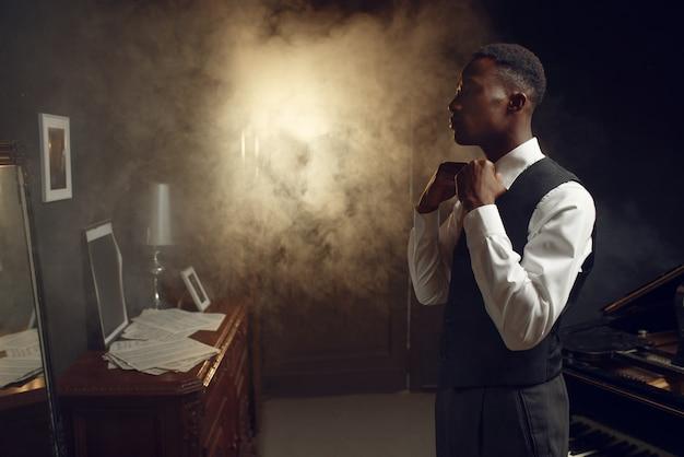 Joueur de piano à queue en ébène, artiste de jazz. l'interprète pose à l'instrument de musique avant de jouer la mélodie