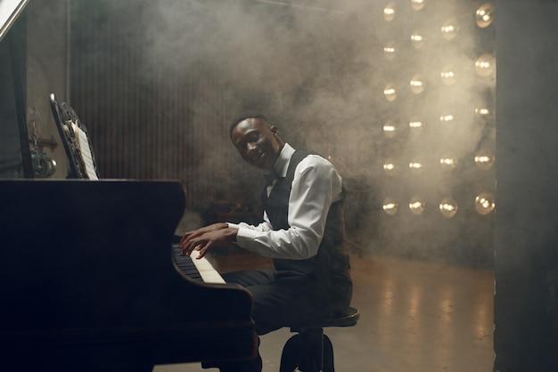 Joueur de piano à queue en ébène, performance de jazz en club. l'interprète pose à l'instrument de musique avant de jouer la mélodie