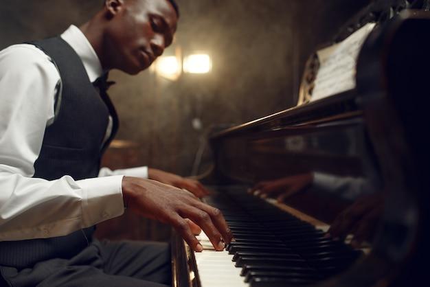 Joueur de piano à queue noir, performance de jazz en club. interprète jouant d'un instrument de musique
