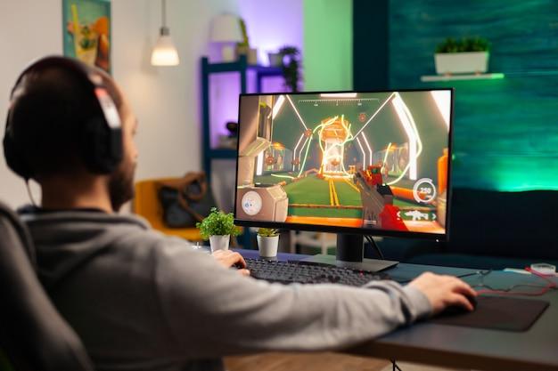 Joueur professionnel jouant sur un jeu vidéo informatique pour un tournoi à l'aide d'écouteurs professionnels. cyber-streaming en ligne lors d'une compétition de jeu à l'aide d'un réseau technologique sans fil