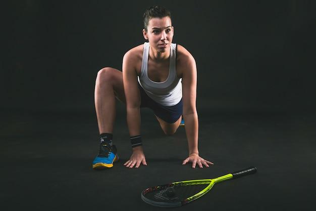 Joueur de squash étirant ses jambes