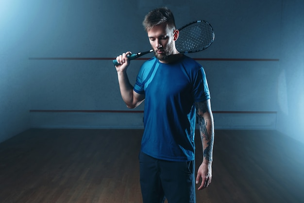 Joueur de squash avec raquette, terrain d'entraînement intérieur