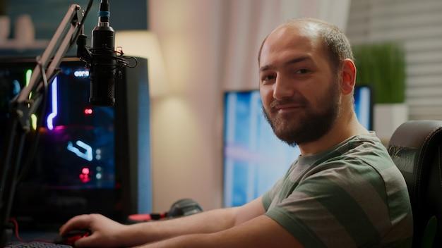 Joueur de streamer focalisé regardant la caméra préparant un jeu vidéo en ligne de tireur d'espace en streaming jouant sur un ordinateur puissant rvb pendant le championnat egames. esport cyber performant dans un tournoi de jeu