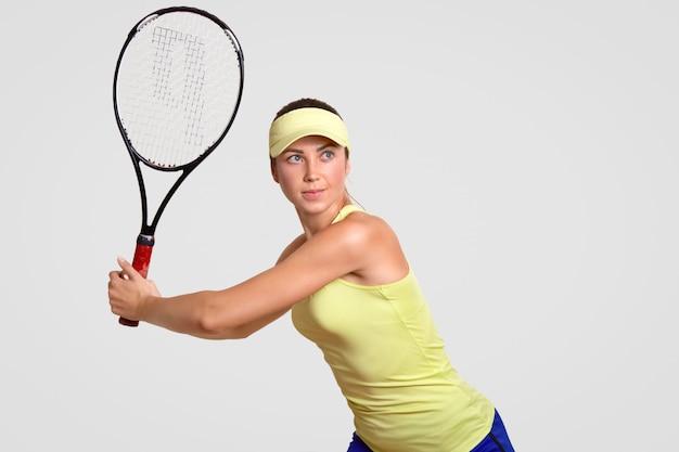 Joueur de tennis actif vêtu d'une casquette de court, d'un t-shirt et d'un short, tient une raquette, se prépare pour la compétition, veut gagner le match, se tient contre le mur blanc. concept de personnes, jeu, style de vie et passe-temps