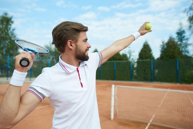 Le joueur de tennis attrape une balle de tennis