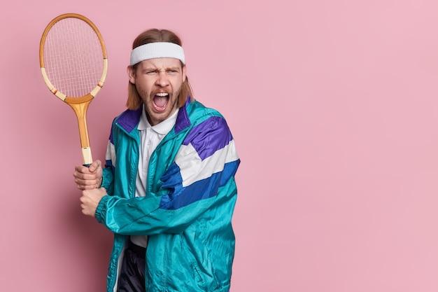 Un joueur de tennis barbu s'exclame bruyamment.