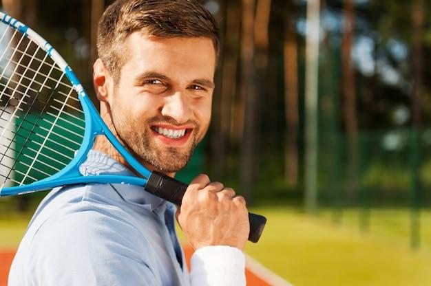 Joueur de tennis confiant. vue latérale d'un jeune homme heureux en polo portant une raquette de tennis sur l'épaule et souriant en se tenant debout sur un court de tennis