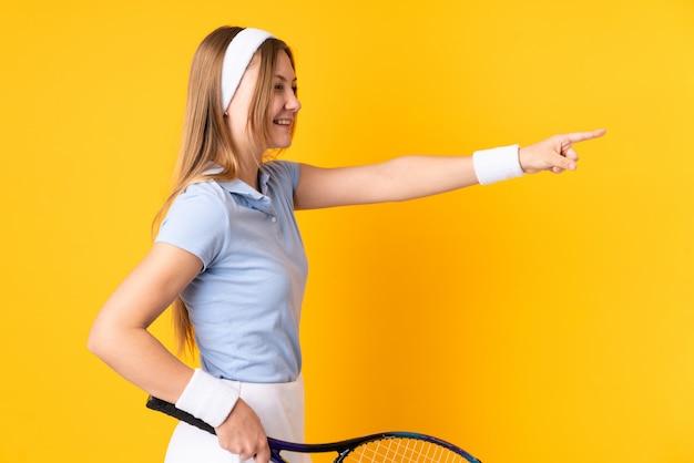 Joueur de tennis femme ukrainienne adolescent isolé sur espace jaune jouant au tennis