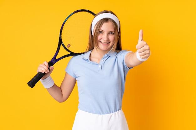 Joueur de tennis femme ukrainienne adolescent isolé sur espace jaune jouer au tennis et avec le pouce vers le haut