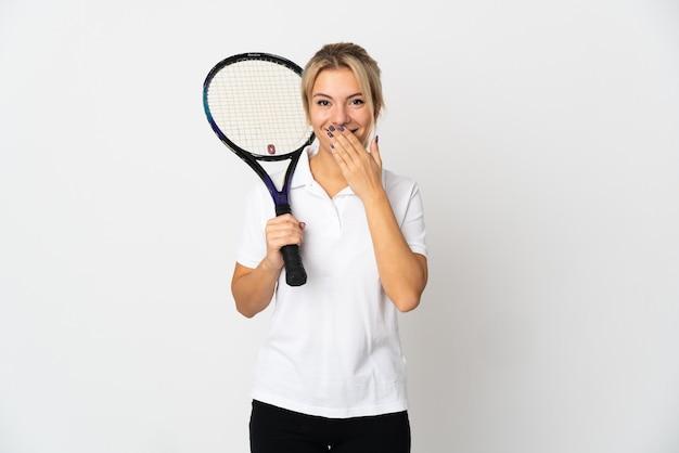 Joueur de tennis jeune femme russe isolé sur blanc heureux et souriant couvrant la bouche avec la main