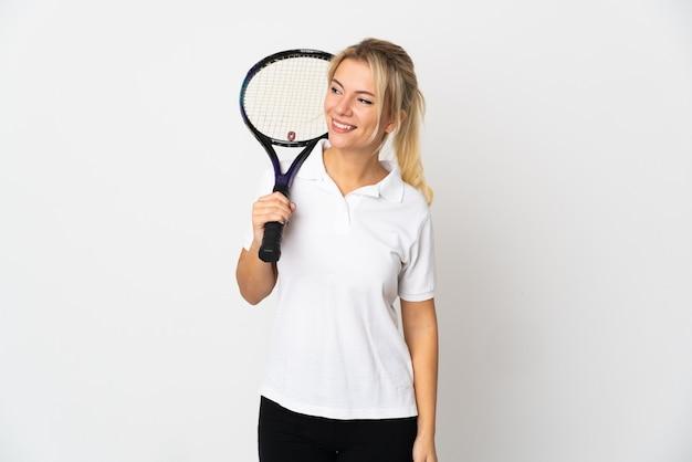 Joueur de tennis jeune femme russe isolé sur blanc à la recherche sur le côté et souriant
