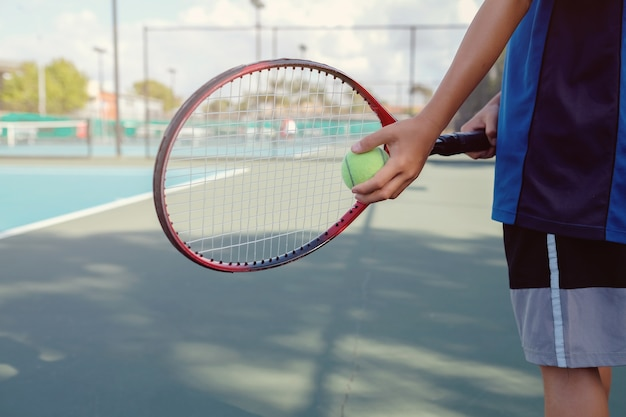 Joueur de tennis jeune garçon sur un terrain bleu
