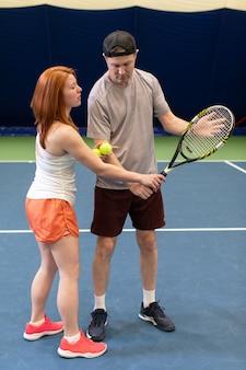 Joueur de tennis recevant des instructions de l'entraîneur sur la façon de jouer sur un court intérieur. instructeur féminin explique la technique de frappe à son élève