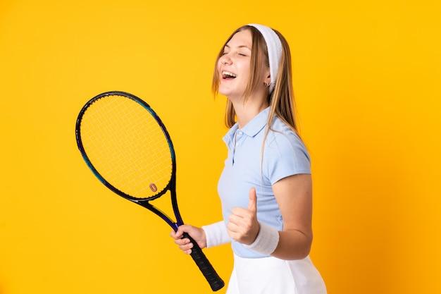 Joueur de tennis ukrainien adolescent isolé sur un espace jaune en jouant au tennis et célébrant une victoire
