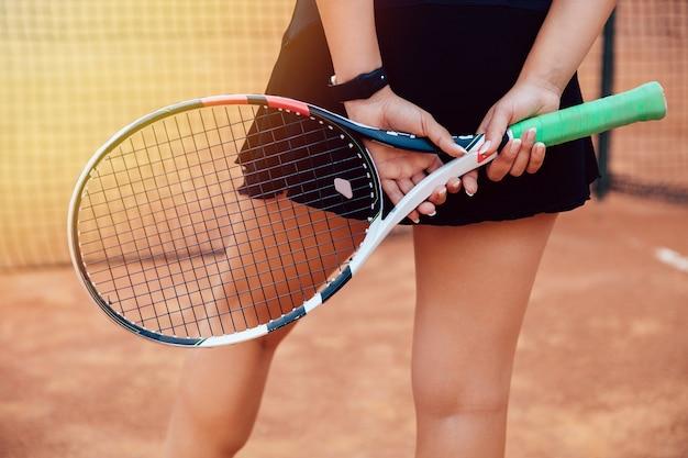 Joueur de tennis. vue arrière d'une femme sportive avec une raquette de tennis tenant derrière le dos