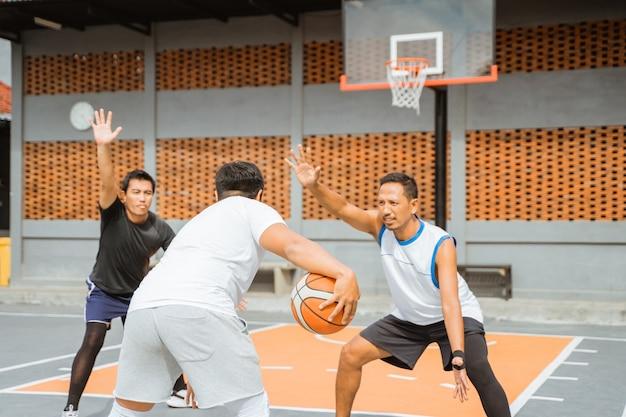 Le joueur tient le ballon en tirant trois points dans le cerceau
