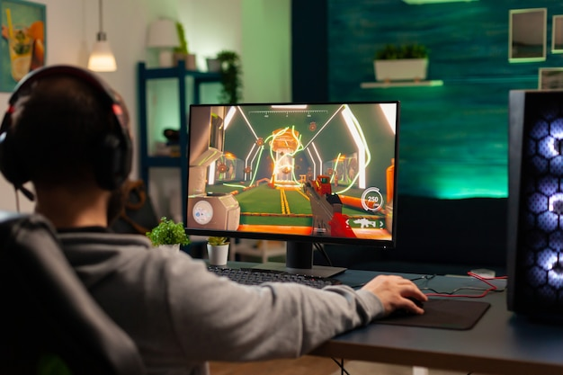 Joueur vidéo à la recherche d'un ordinateur puissant jouant à un jeu de tir virtuel tard dans la nuit dans le salon. cyber streaming en ligne lors d'un tournoi de jeu à l'aide d'un réseau technologique sans fil