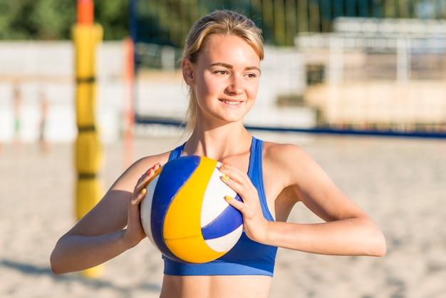 Joueur de volley-ball féminin smiley sur la plage tenant le ballon