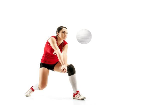 Joueur de volley-ball professionnel féminin avec ballon isolé sur fond de studio blanc. l'athlète, l'exercice, l'action, le sport, le mode de vie sain, l'entraînement, le concept de remise en forme. la fille en mouvement
