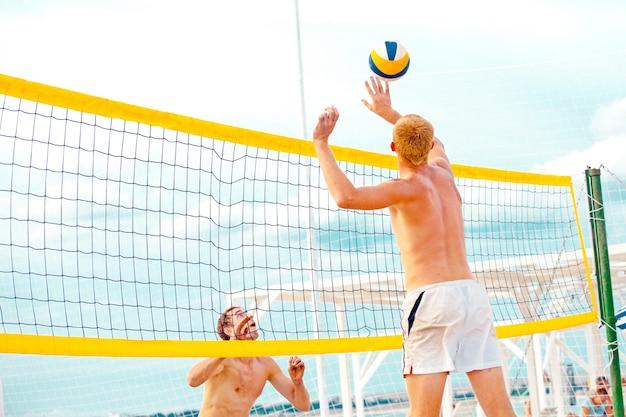 Un joueur de volleyball sur la plage est un athlète masculin qui se prépare à servir le ballon sur la plage.