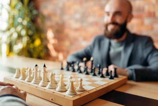 Les joueurs d'échecs masculins commencent à jouer, concentrez-vous à bord avec des chiffres.