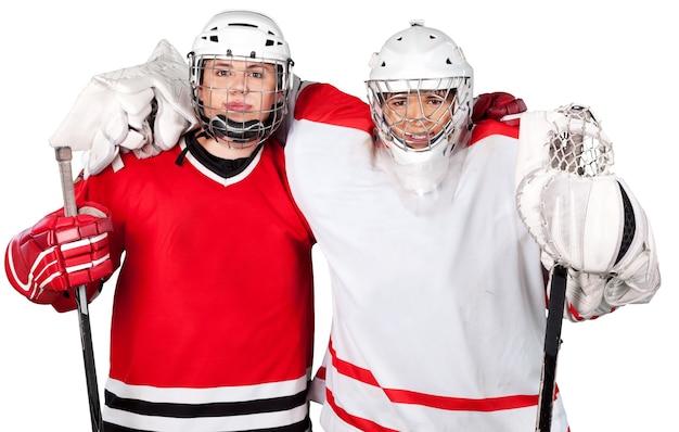 Joueurs de hockey sur glace masculins dans des casques tenant des bâtons de hockey sur fond blanc