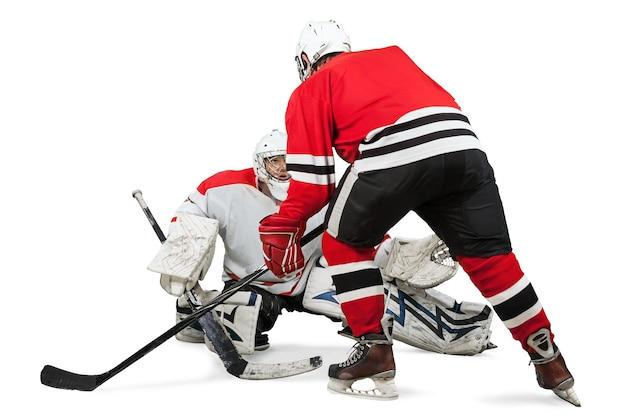 Joueurs de hockey sur glace masculins dans des casques tenant des bâtons de hockey et jouant sur un fond blanc