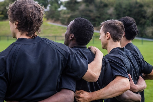 Les joueurs de rugby debout ensemble avant le match au parc