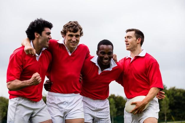 Joueurs de rugby mettant les mains ensemble