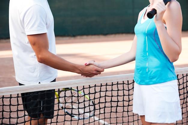Joueurs de tennis recadrés se saluant sur le terrain