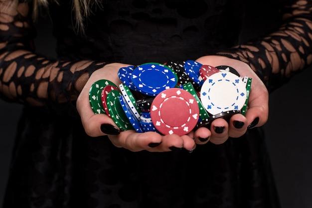 Joueuse de casino élégante tenant une poignée de jetons sur fond noir, les mains se bouchent. poker. casino. roulette blackjack spin.