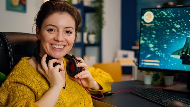 Joueuse d'esport professionnelle souriante à la caméra tout en participant à un jeu vidéo lors d'un événement de championnat. cyber streaming en ligne s'exécutant sur un ordinateur personnel puissant pendant un tournoi de jeu