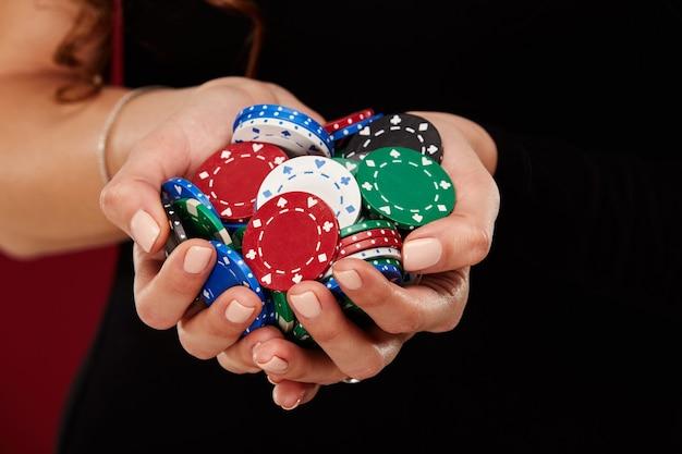 Une joueuse de poker avec des ongles blancs peints tient ses jetons de poker pour faire un pari. concept d'entreprise de jeu et de casino