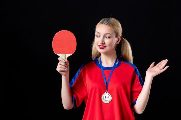 Joueuse avec raquette et médaille d'or sur fond noir athlète vainqueur du trophée