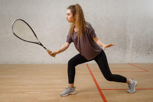 Joueuse avec raquette de squash en action. fille sur la formation de jeu, passe-temps sportif actif sur le terrain