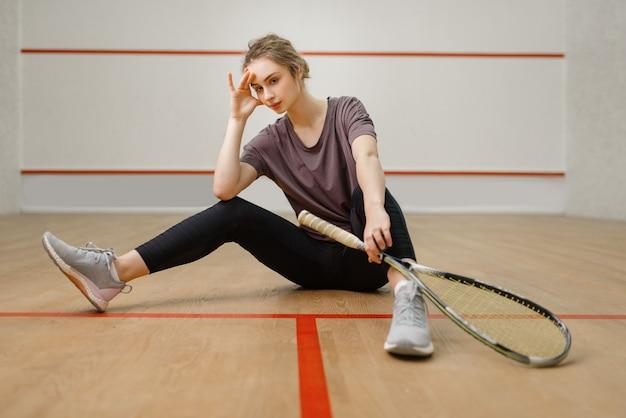Joueuse avec raquette de squash assis sur le sol