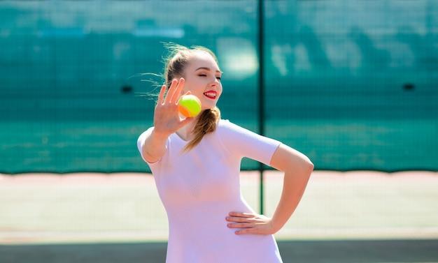 Joueuse en robe blanche et talons tenant une raquette de tennis. jeune femme joue au tennis, sport