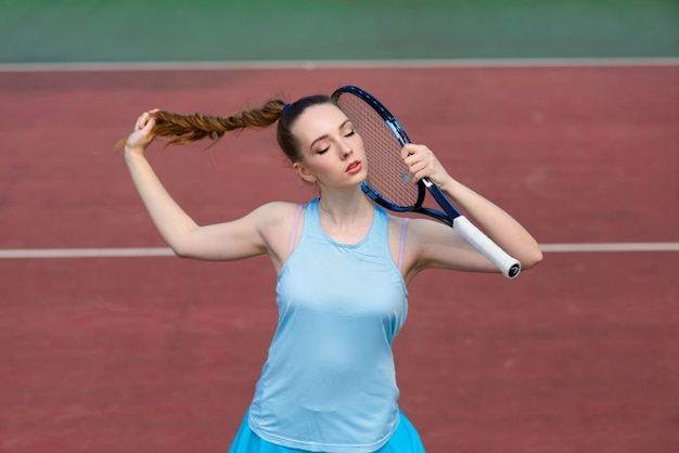 Joueuse de tennis fille sexy en robe blanche et talons tenant une raquette de tennis sur le court. jeune femme joue au tennis, sport