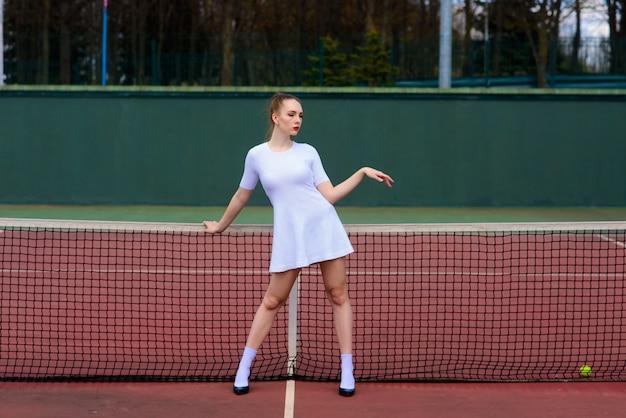 Joueuse de tennis fille sexy tenant une raquette de tennis sur le terrain. jeune femme joue au tennis.