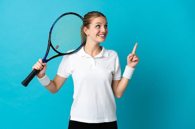 Joueuse de tennis jeune femme isolée sur bleu pointant vers le haut une excellente idée
