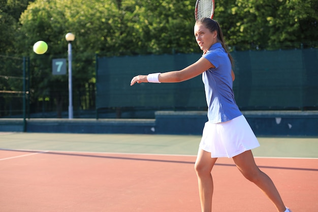 Joueuse de tennis professionnelle équipée battant fort la balle de tennis avec une raquette.