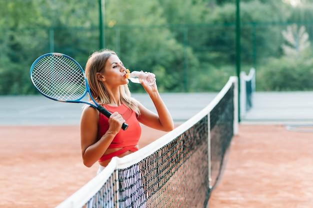 Joueuse de tennis avec une serviette sur ses épaules l'eau potable après le match