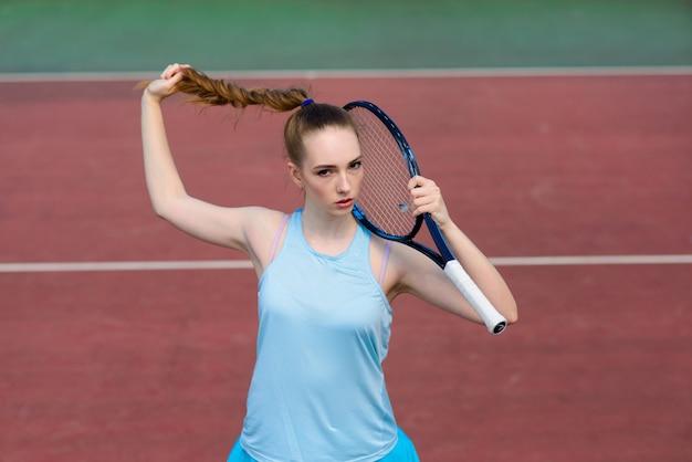 Joueuse de tennis tenant une raquette de tennis sur le terrain. la jeune femme joue au tennis.
