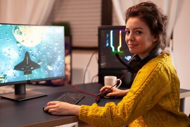 Joueuse en train de décoller le siège en regardant la caméra en souriant et en jouant dans un championnat de jeu de tir virtuel dans le cyberespace, joueur d'esport se produisant sur un ordinateur dans une pièce élégante pendant un tournoi de jeu