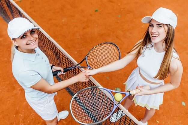 Joueuses de tennis à la recherche de plaisir à la caméra sur un court en terre battue avec une partenaire.