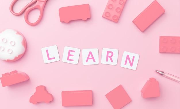 Jouez et apprenez avec des jouets et des objets pour le concept d'éducation de l'enfant sur fond rose