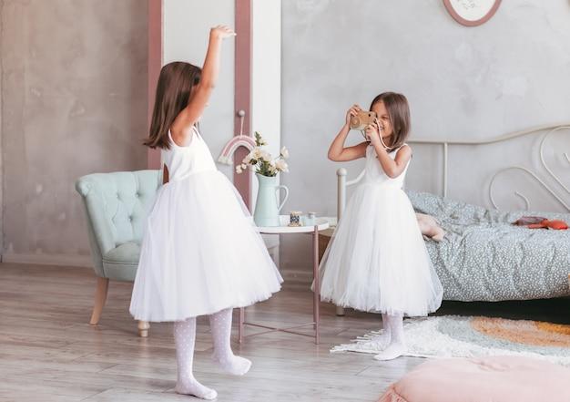 Jouez à deux filles dans une grande pièce lumineuse. les deux sœurs passent du temps heureux ensemble