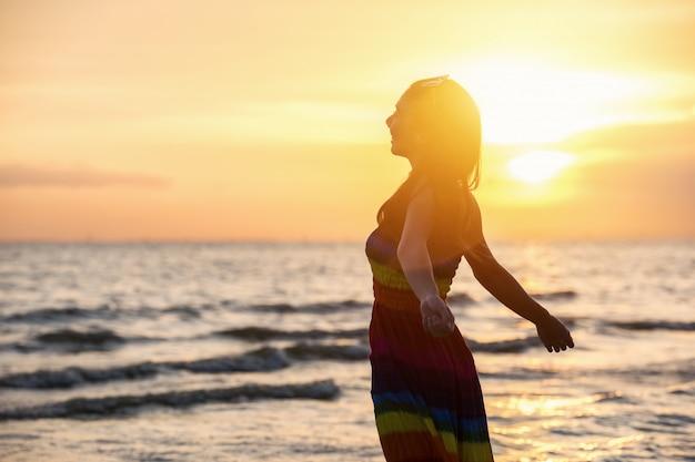 Jouissance - femme heureuse libre en admirant le coucher du soleil.