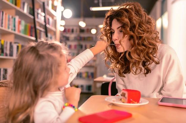 Jouons. petite femelle consciente nourrir sa mère tout en passant du temps libre au café ensemble
