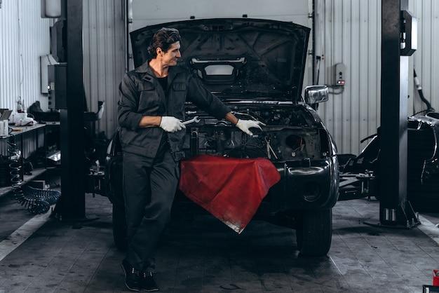 Jour de chance. homme adulte souriant en uniforme de travail posant debout près de la voiture ouverte noire dans le grand garage automobile